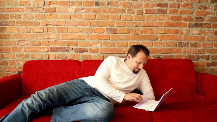 Lying man working on laptop