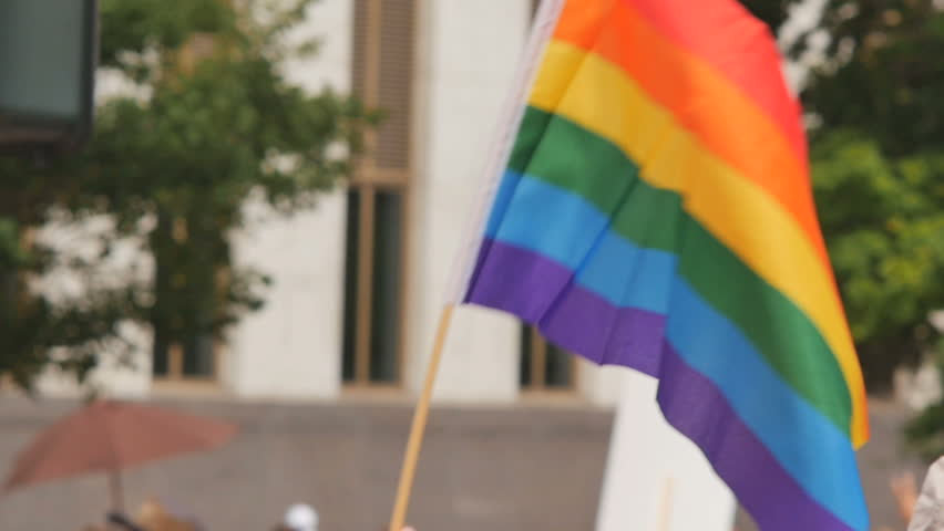 A rainbow flag waves as people walk by in the background with other rainbow flags and protest signs. slow motion. Symbol of LGBT GLBT transgender rights love equality  | Shutterstock HD Video #10756754