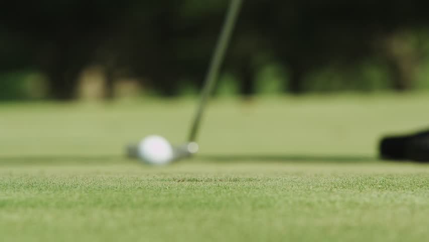 Close up of a guy missing a put at the golf course.