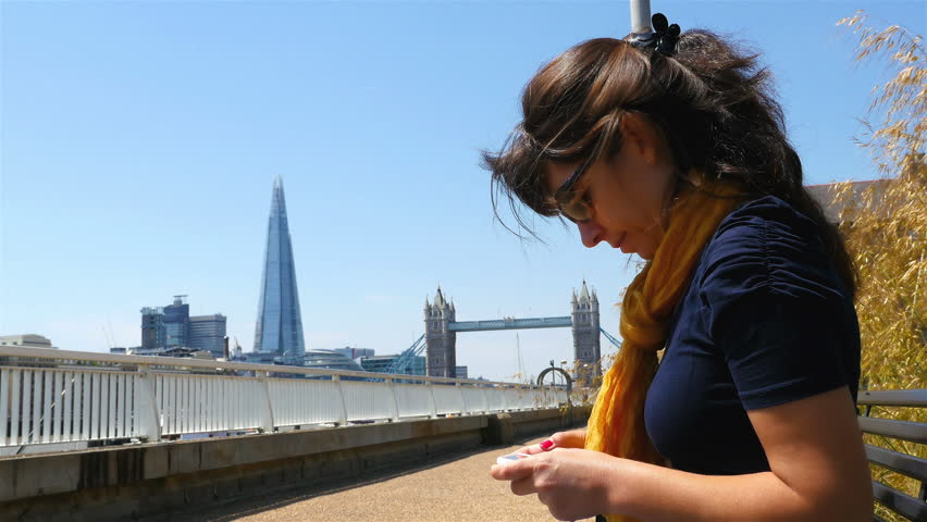 Young woman sending an sms with a mobile phone with London Tower bridge and Shard in background | Shutterstock HD Video #10843907