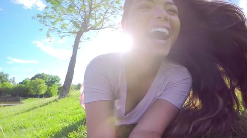 Beautiful Asian Teen Holds A camera And Rolls Down A Huge Grassy Hill In A Park (Slow Motion)