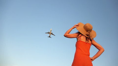 Airplane flying overhead, girl watching and waving