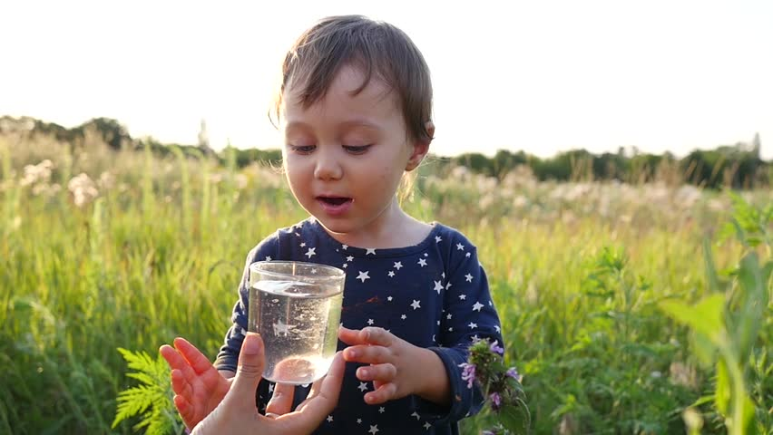Mother gives child daughter drink clean pure water on sunset nature