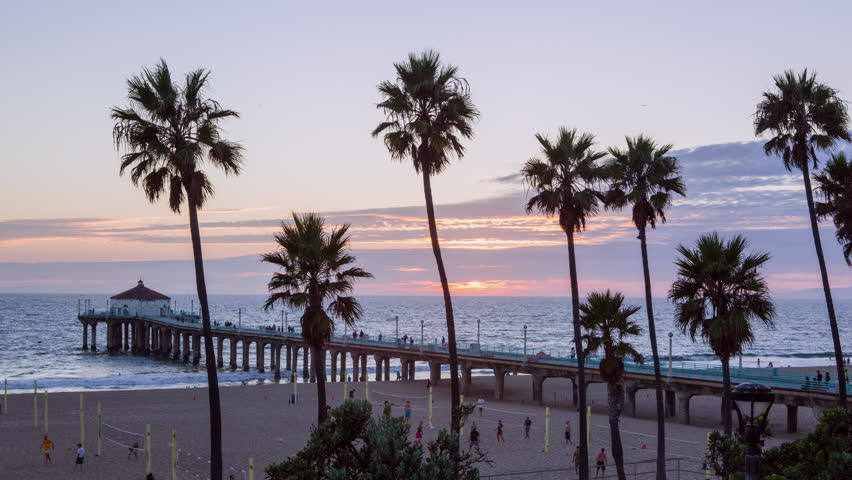 Manhatten Beach, California - October 2014: Timelapse at Manhattan Beach in California with pier out in to the Pacific Ocean. People playing volleyball in fast motion.