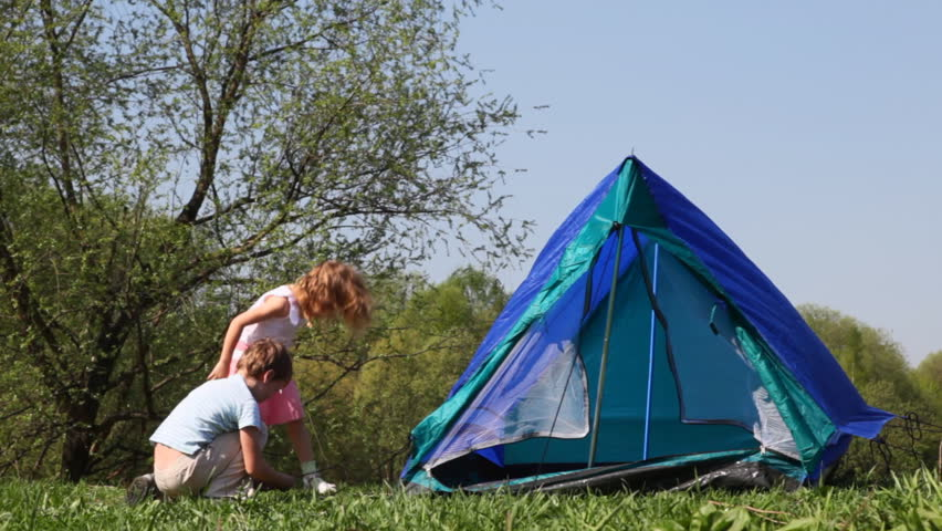 boy and little girl pull cords of tent in woods hot summer
