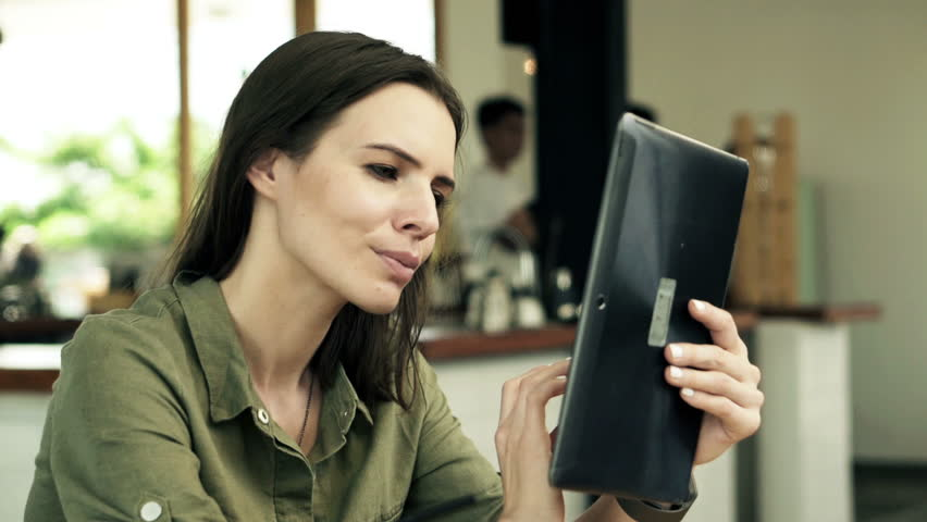Young happy woman with tablet computer sitting in cafe