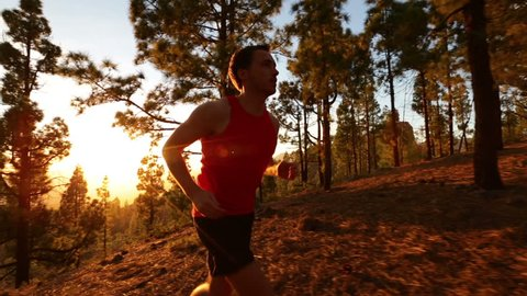Running runner man athlete training outdoors exercising on mountain forest trail at sunset in amazing landscape nature. Fit handsome athletic male working out for marathon run outside in summer.