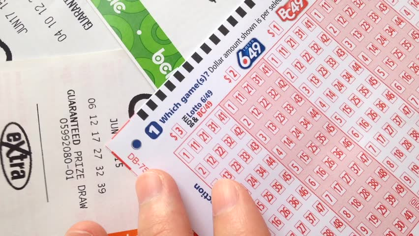 Coquitlam, BC, Canada - July 23, 2015 : Woman Hands Filling Lucky Number  Non 6/49 Lottery Ticket. Lotto 6/49 Is One Of Two National Lottery Games In  Canada.