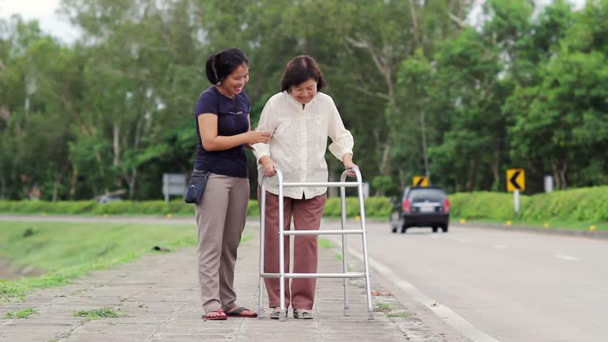 Senior woman using a walker cross street with assistance.