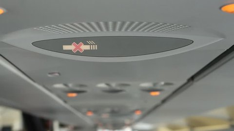 A detailed head on shot of  the dash board above the seats on an airplane, The icon indicating that seat-belts must be put on appears to the right of the dash board screen.