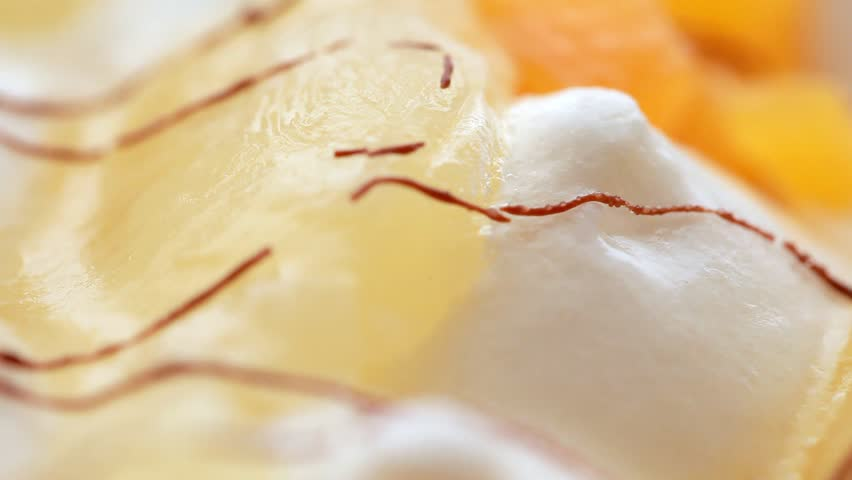 closeup of sweet ice-cream with fruit slices, rotate