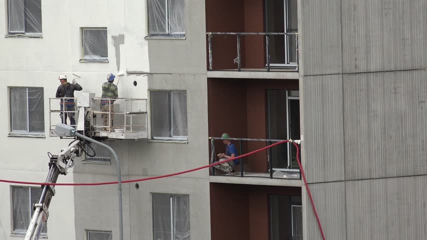 VILNIUS, LITHUANIA - MAY 28, 2015: Constructors men in crane lift paint new modern flat house wall with roller in white color on May 28, 2015 in Vilnius, Lithuania. Zoom out shot. 4K | Shutterstock HD Video #10965287