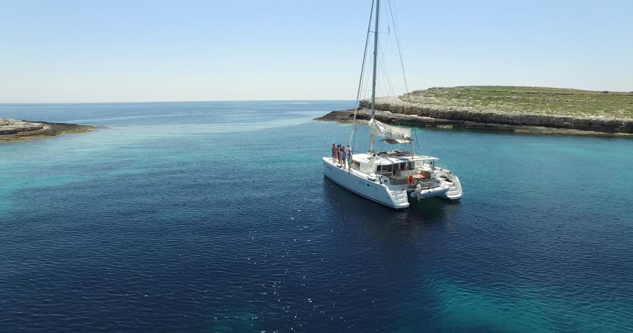 Aerial scene of catamaran anchored in virgin coast. Natural landscape. Camera rises to a panoramic view. Beautiful picture, transparent, turquoise water. Turistic place.