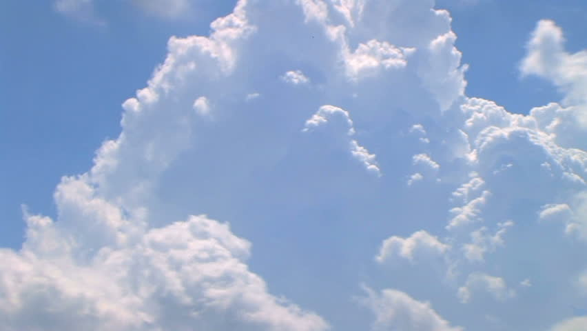 Time lapse of beautiful cumulus clouds rolling through bright blue sky.
