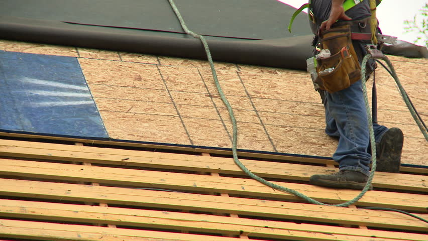 Construction Workers Install A New Roof On House They Use Ropes And Harnesses For Safety Tool Belts Boots Are Worn Slats Exposed