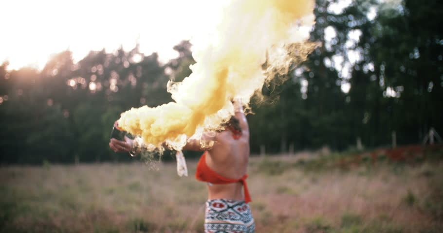 Boho girl walking in field carrying smoke flares releasing clouds of yellow smoke