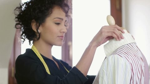 Woman and business, women and fashion industry, female designer in studio, young dressmaker adjusting clothes on tailoring mannequin and smiling at camera. Dolly shot
