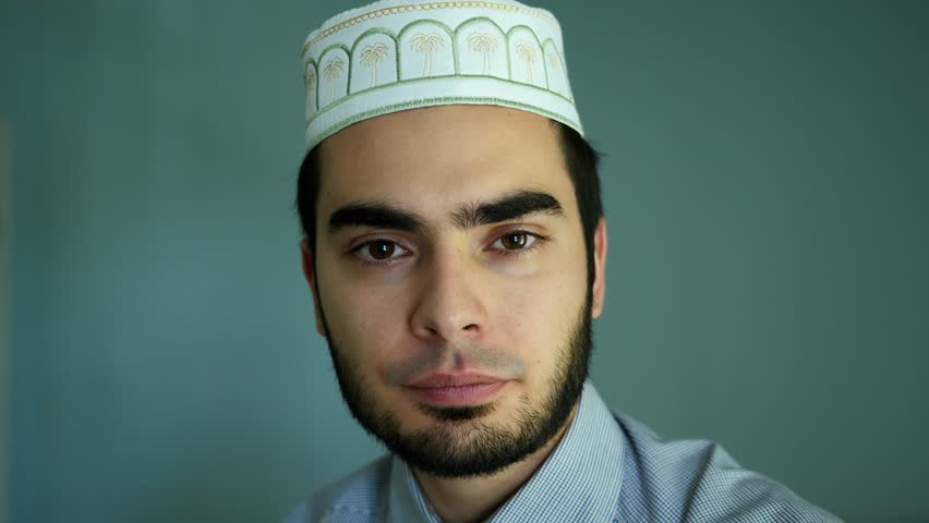 Portrait of a attractive young arabic muslim man wearing a typical beard and hat. Looking directly to the camera. Filmed in UHD 4K resolution.