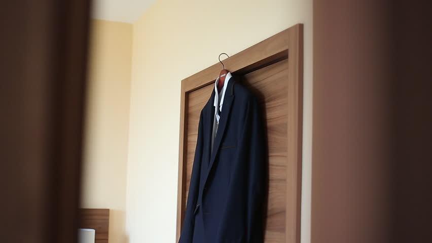 Groom's suit hanging on the door frame