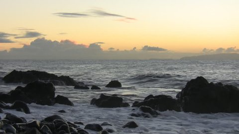Atlantic ocean waves splash against rocks before sunrise in the early morning at the Madeira island black stone beach with Desertas islands on the horizon
