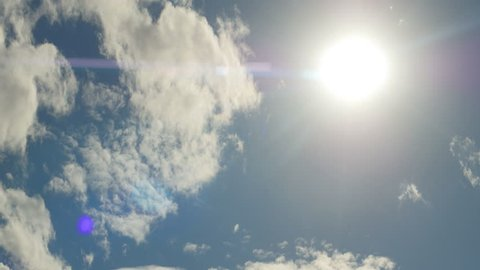 Clouds, time lapse. White clouds flying on blue sky with sun rays. Anamorphic lens. 4k footage.