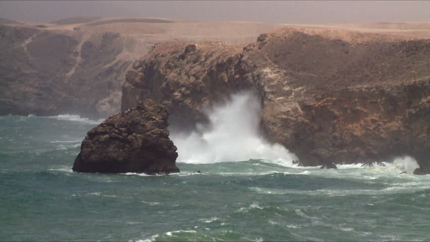 The choppy sea and waves come in and break onto the rocky coastline in Salalah, Oman