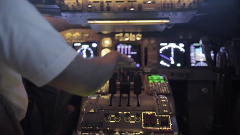 Detail shot of airline pilot pulling back on jet throttles in the cockpit of a jumbo jet.  Rear view, hand-held with fast changing movement and racking focus, originally recorded in 4K.