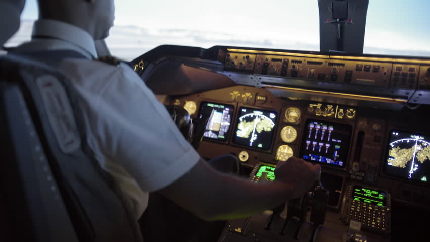 Rear angle view over pilot's shoulder as he takes off in a jumbo jet.  Hand-held camera, medium close, with tilt from throttles to windows, originally recorded in 4K at 30fps.
