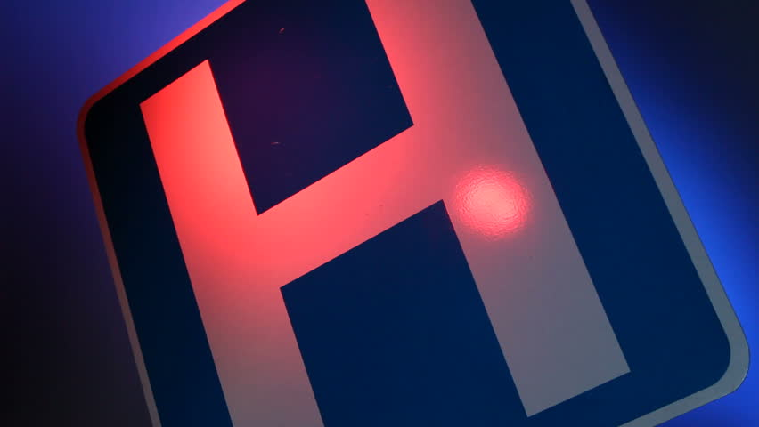 A close up of a hospital sign with flashing red and blue lights reflected on the
