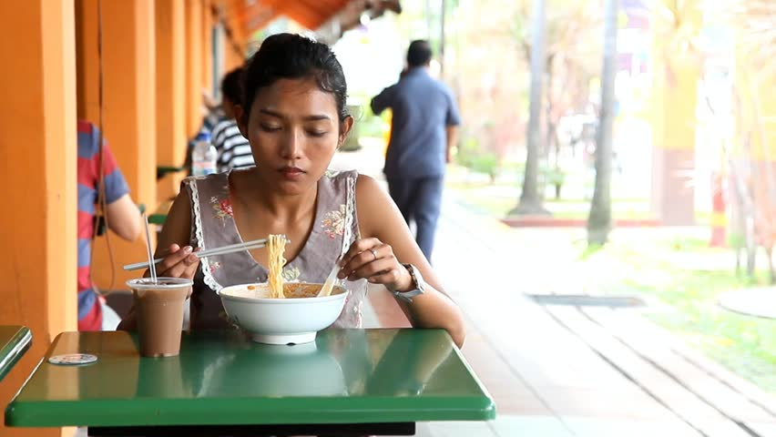 Young Asian woman eating a bowl of noodles at a table in a Chinese  restaurant -