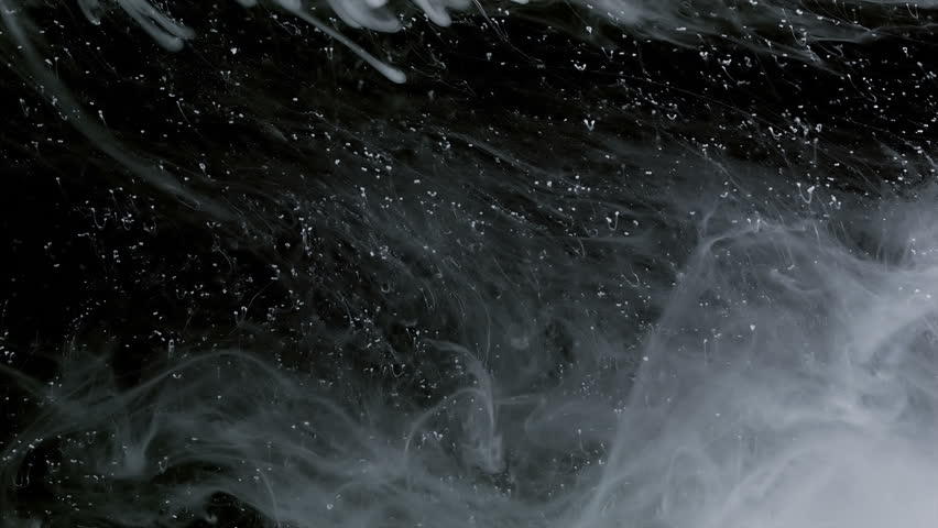 Veil of ink and particles on black background floating slowly trough space, close up