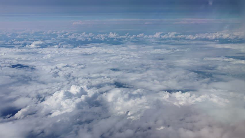Traveling by air above clouds. View through an airplane window. Flying over the Mediterranean Sea through cirrus and cumulus clouds and little turbulence, showing Earth's atmosphere. | Shutterstock HD Video #11192837