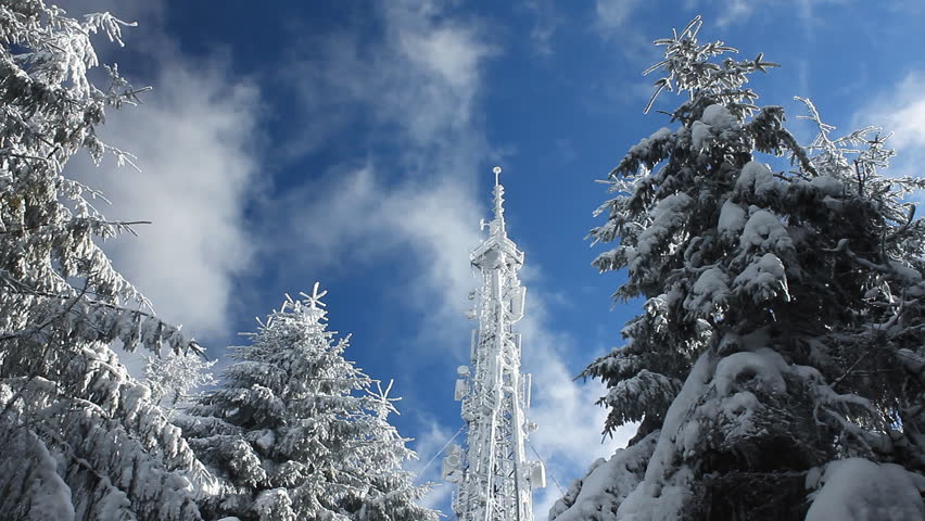 Cellular tower in snow on a blue sky background with clouds passing by | Shutterstock HD Video #1122997