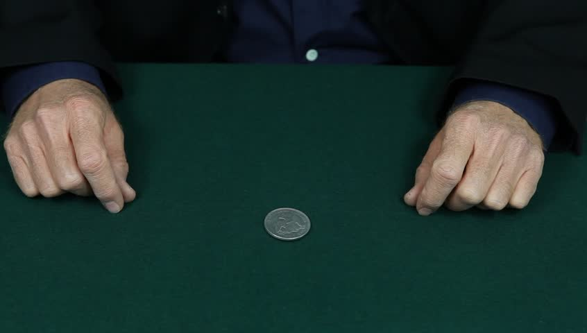 Magician changes a silver dollar to a penny.