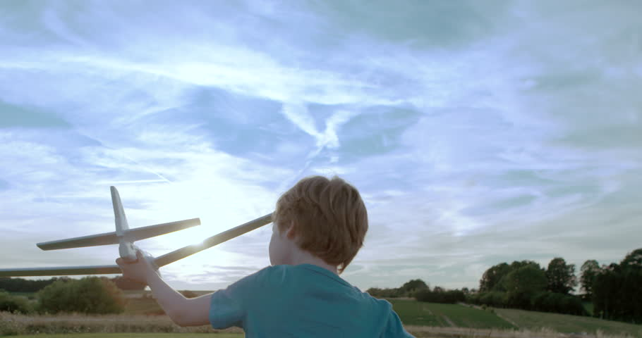 Boy playing outdoors with toy airplane at sunset...