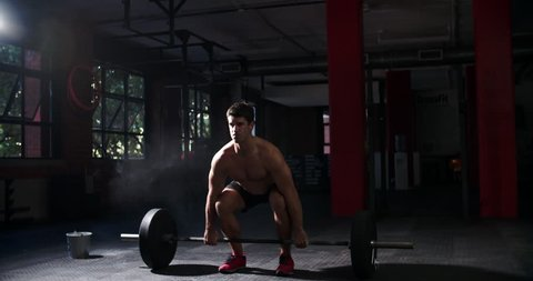 Bare chested man weightlifting barbells in a gym