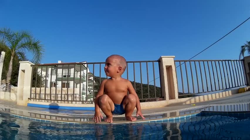 Skinhead toddler sits on the edge of the swimming pool