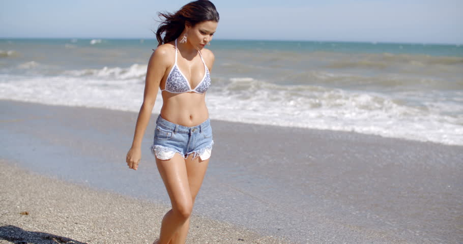 Alluring attractive young woman in skimpy shorts with a bare midriff standing at the seaside with her hand to her windblown hair and the ocean behind her smiling at the camera.