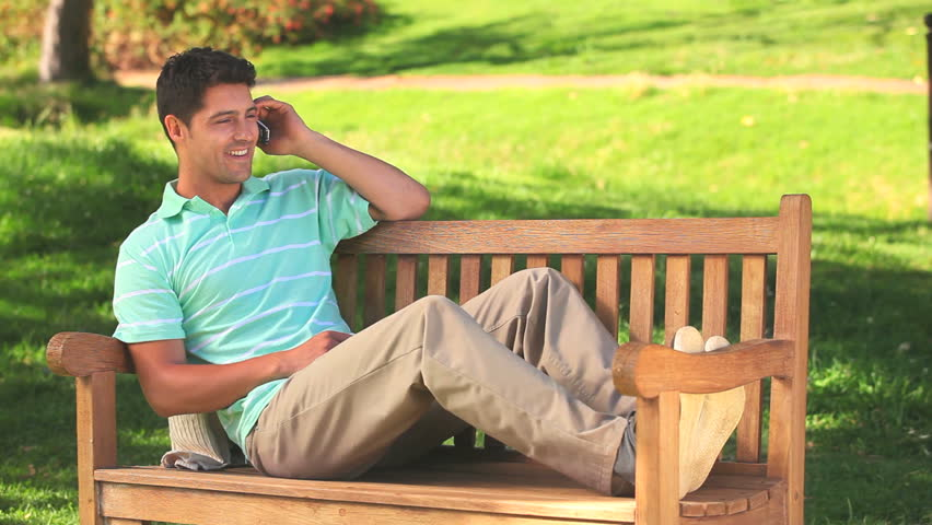 Lying Man On A Park Bench Speaking On The Phone
