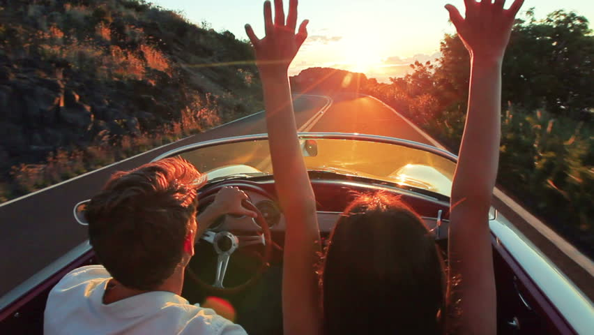 Couple driving convertible car. steadicam shot with flare into sunset in Hawaii