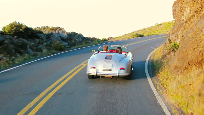 Happy Couple Driving on Country Road into the Sunset in Classic Vintage Sports Car. Cabriolet Steadicam Shot.