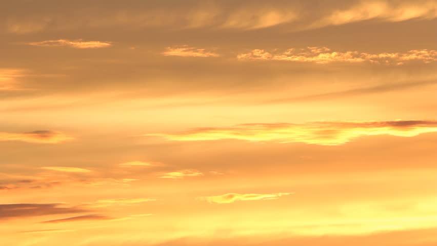 Pale Orange light colored orange clouds on pale blue twilight sky stock