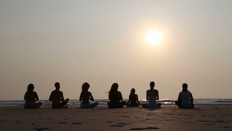 GOA, INDIA - 19 JANUARY 2015: People practicing yoga at a sandy beach in Goa at sunset.
