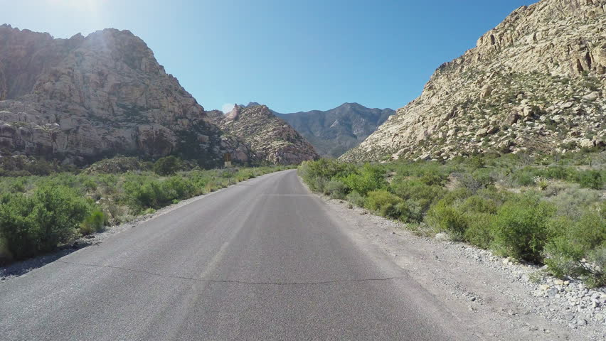 Point of view of a motorcyclist in riding bike through Red Rock Canyon in 4K format. A biker rolls down an empty scenic stretch of road near Las Vegas Nevada.