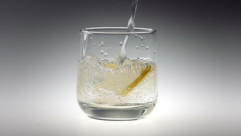 180fps Super Slow Motion Sparkling Water and Lemon Falling into Glass