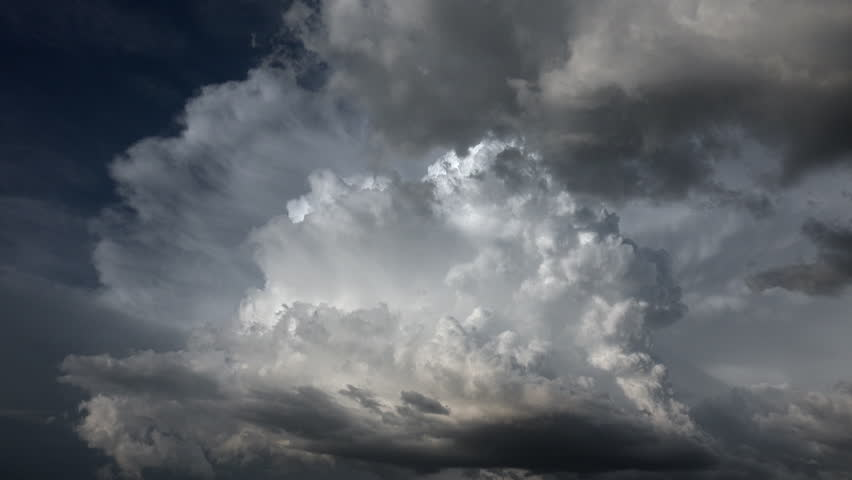 Time Lapse, Dramatic light creates glow around beautiful cloudburst, quickly swallowed by dark storm clouds, blue sky background. 4K UHD 3840x2160