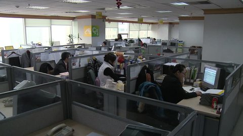 Chengdu, China - March 2010: A modern Chinese office with workers at their computers in cubicles in Chengdu, China.