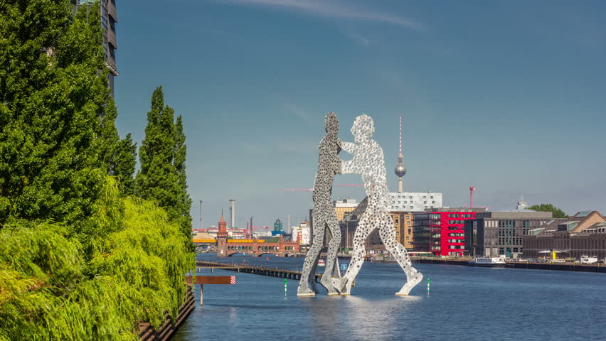 """BERLIN, GERMANY - JULY 16, 2013: Skyline of Berlin and the sculpture """"Molecular men"""" in the foreground and the river Spree, Berlin, Germany. Timelapse, hyperlapse view 4K."""