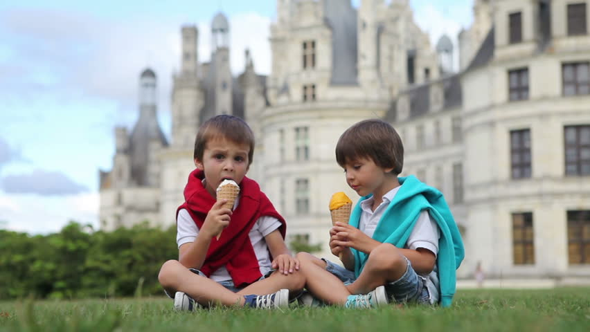 Funny children kids, little boys, eat ice cream on a lawn in the park in front of a big castle in France, Chambord