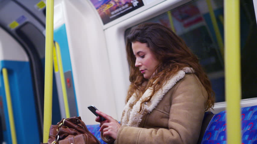4k Relaxed, young female using smartphone on subway underground train. Shot on RED Epic. | Shutterstock HD Video #11518457